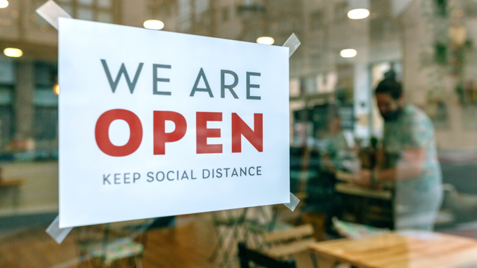 A sign on a restaurant window explaining that the restaurant is open and requesting social distance