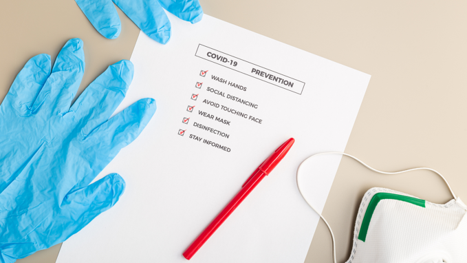 A tradeshow safety checklist with latex gloves and a mask