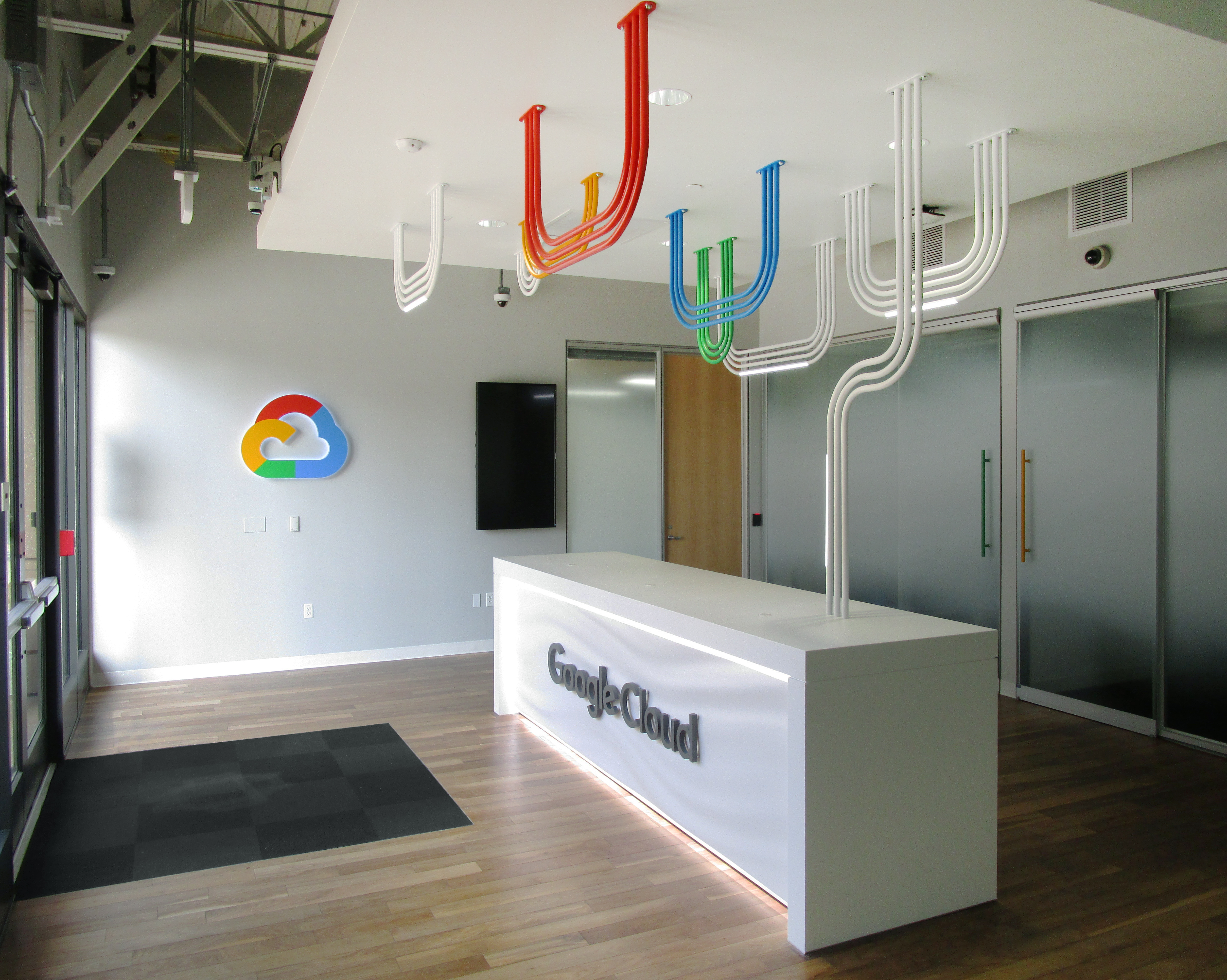 Google cloud reception counter with google cloud logo on the wall and pipes to create clouds above desk